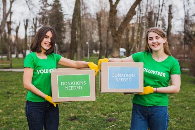 Ambiente e conceito de voluntariado com pessoas segurando caixas para doações