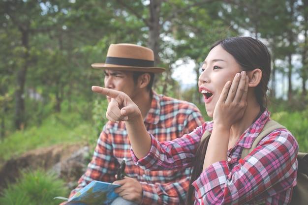 Ambos os amantes são felizes nas colinas da floresta tropical, caminhadas, viajar, escalar.