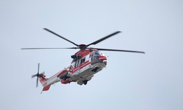 Ambulância, helicóptero militar ou civil no fundo do céu.