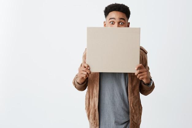 Amd. close-up de jovem bonito engraçado macho de pele preta com penteado afro em camiseta sob o casaco marrom, fechando o rosto com placa da caixa, olhando na câmera com expressão de surpresa