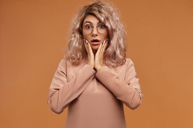 Amd. foto da aluna engraçada emocional com argola no nariz, expressando choque. jovem chocada e surpresa usando óculos redondos e abrindo bem a boca