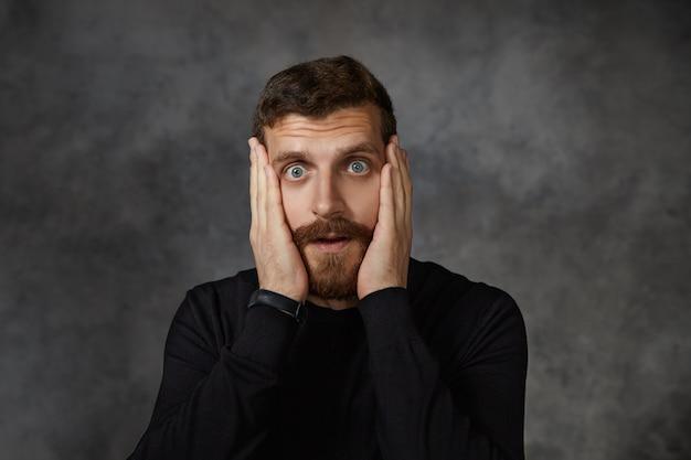 Amd. frustrado chocado espantado jovem barbudo com bigode aparado mantendo as mãos no rosto e olhos arregalados, reagindo emocionalmente a notícias inesperadas e surpreendentes
