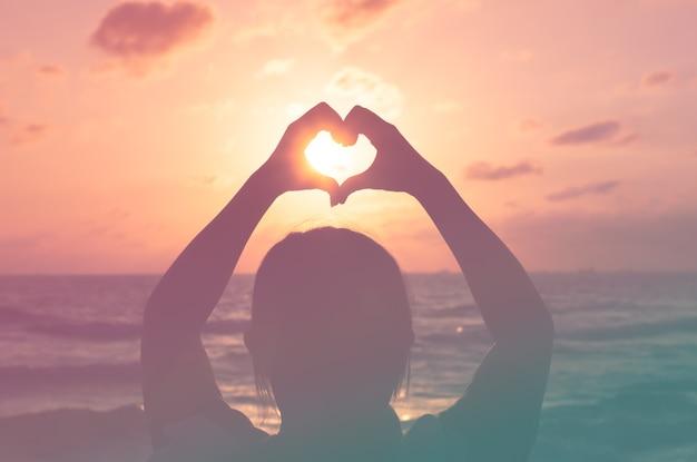 Ame a silhueta da mão da forma no por do sol ou no período dunrise