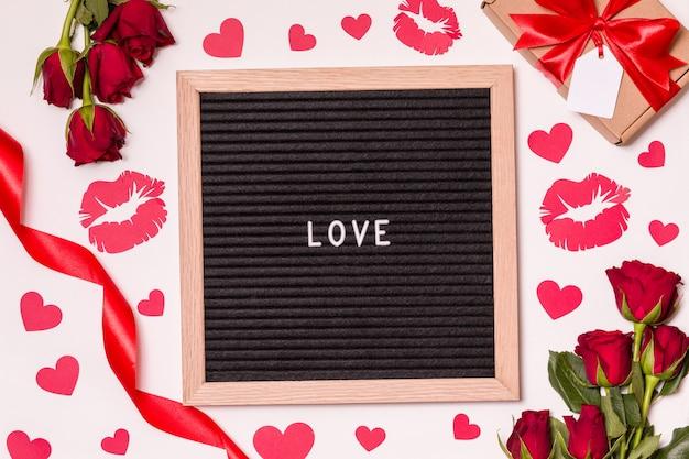 Ame o sinal na placa da letra de feltro com fundo do dia de valentim com rosa, beijo e corações vermelhos.
