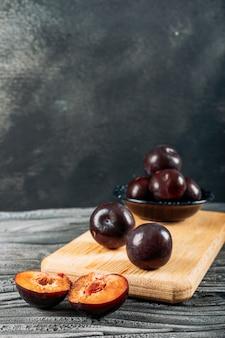 Ameça ameixas cortadas em uma placa de madeira em uma madeira branca e em um fundo cinzento escuro. vista de alto ângulo.