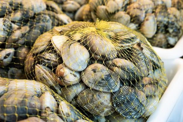 Amêijoas frescas em saco de malha para venda no mercado