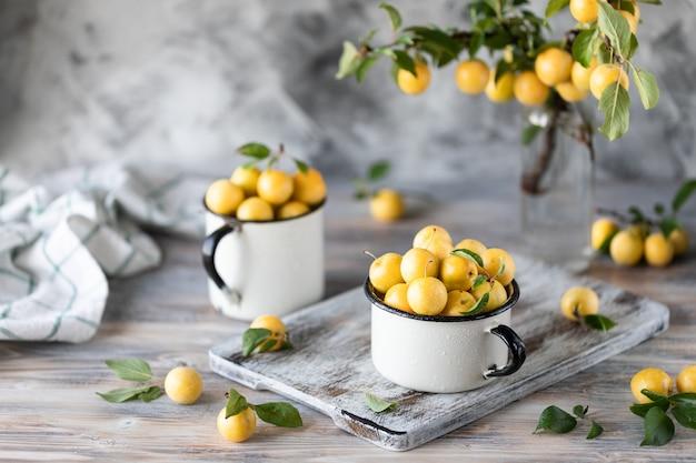 Ameixa amarela nas canecas brancas do ferro na tabela branca. colheita de ameixa de cereja com folhas verdes