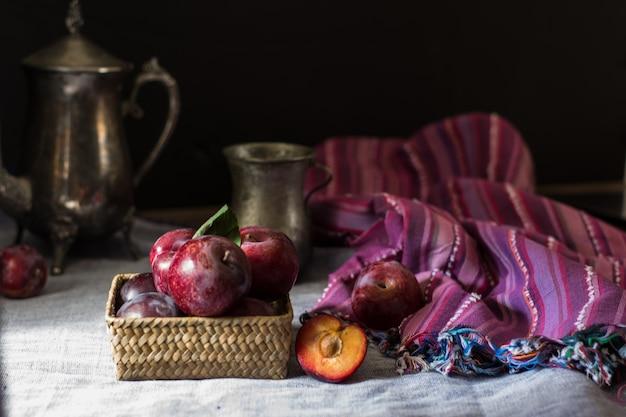 Ameixa fresca. colheita de outono. ameixas vermelhas. ameixa amarela. guardanapo e chaleira vintage e vidro. b
