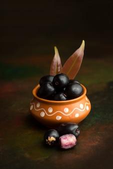 Ameixa jambolan ou jambul ou fruta jamun, ameixa java (syzygium cumini) na mesa texturizada.