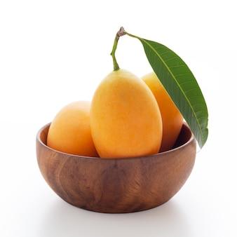 Ameixa mariana ou manga ameixa em uma tigela de madeira isolada no branco
