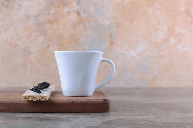 Ameixa seca fatiada no pão crocante e xícara de chá na tábua de madeira, na superfície de mármore