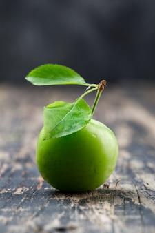 Ameixa verde com as folhas na parede de madeira e suja, vista lateral.