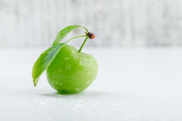 Ameixa verde com as folhas na parede suja e branca, vista lateral.