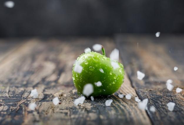 Ameixa verde fria com cristais de sal na parede escura e de madeira, vista lateral.
