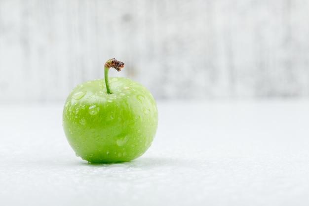 Ameixa verde fria na parede suja e branca. vista lateral.