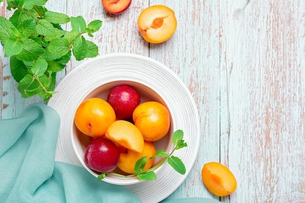 Ameixas amarelas e vermelhas em um prato na mesa de madeira gasta, conceito de frutas de outono, espaço de cópia