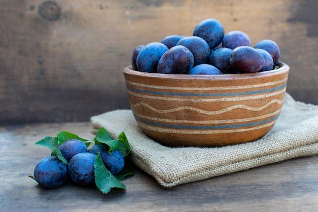 Ameixas azuis maduras em uma textura de madeira