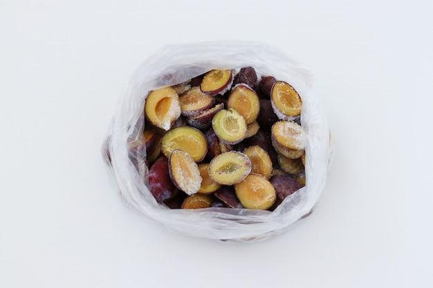 Ameixas congeladas em um pacote transparente isolado no branco