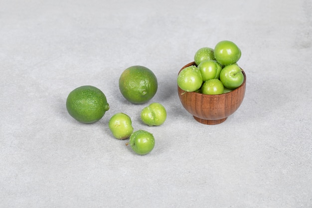 Ameixas de cereja e frutas de limão na mesa da cozinha