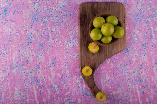 Ameixas de cereja verdes em uma tigela de madeira em uma tábua