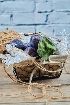 Ameixas de jardim em uma cesta sobre uma mesa de madeira