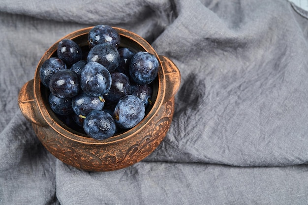 Ameixas de jardim em uma tigela na toalha de mesa cinza. foto de alta qualidade