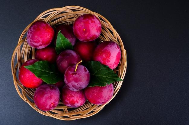 Ameixas doces maduras na bacia de vime. foto