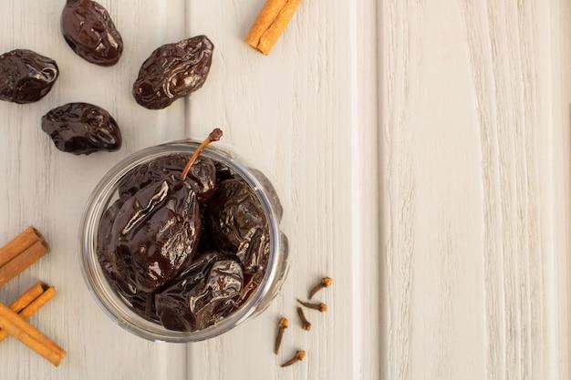 Ameixas em conserva no frasco de vidro sobre a mesa de madeira cinza. produto fermentado. vista do topo. copie o espaço.