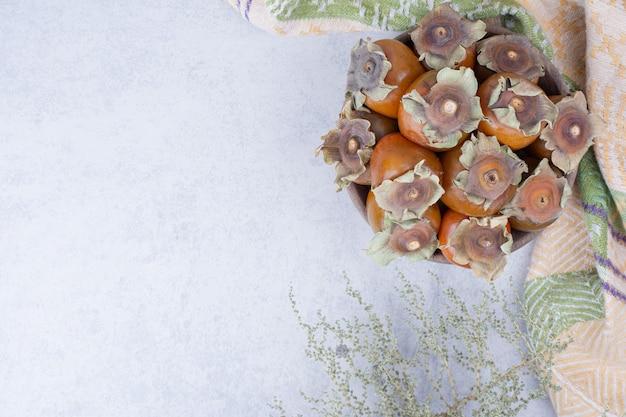 Ameixas em um copo de madeira em um fundo cinza