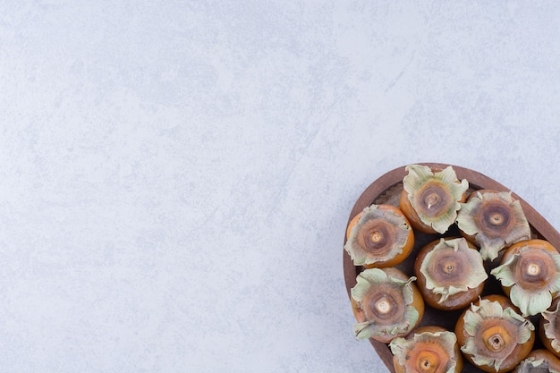 Ameixas em uma bandeja de madeira em fundo cinza