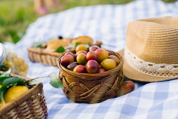 Ameixas em uma cesta de vime e um chapéu de palha em uma toalha xadrez azul e branca