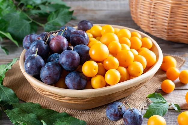 Ameixas frescas, ameixas cereja com folhas em uma mesa de madeira
