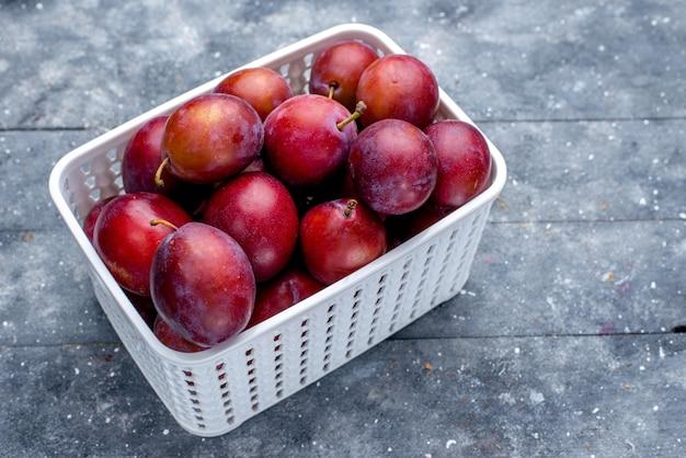 Ameixas frescas azedas dentro de uma cesta branca em cinza, frutas frescas azedas maduras