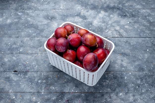 Ameixas frescas azedas dentro de uma cesta branca em cinza
