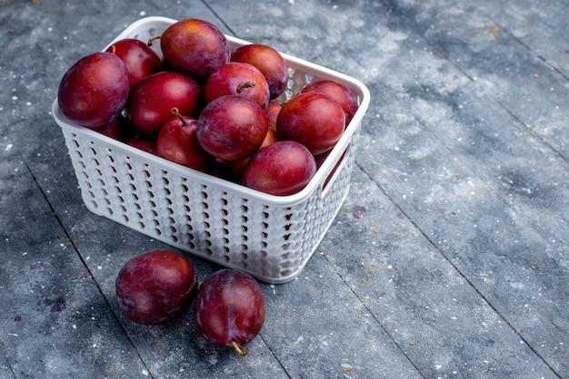 Ameixas frescas azedas dentro de uma cesta branca em uma mesa leve, frutas frescas azedas maduras, foto