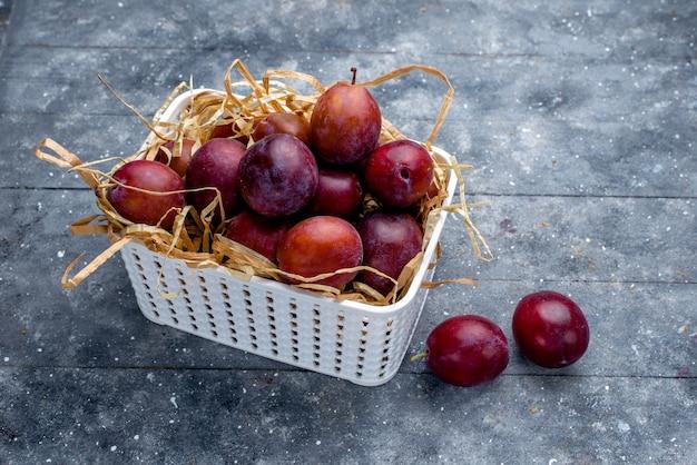Ameixas frescas dentro de uma cesta branca em cinza