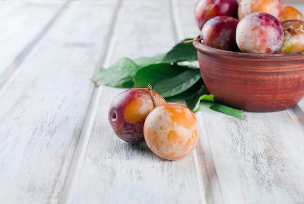 Ameixas frescas do jardim na bacia na tabela de madeira velha.