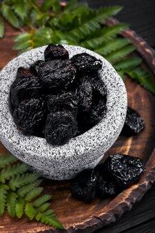 Ameixas frescas em uma tigela de pedra. ameixas secas na mesa de pedra escura. ameixas alimentares saudáveis. ameixas secas em uma tigela.