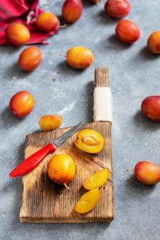 Ameixas frescas maduras em uma tábua