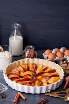 Ameixas frescas maduras na torta caseira, ingredientes de cozimento e utensílios de cozinha para cozinhar e assar