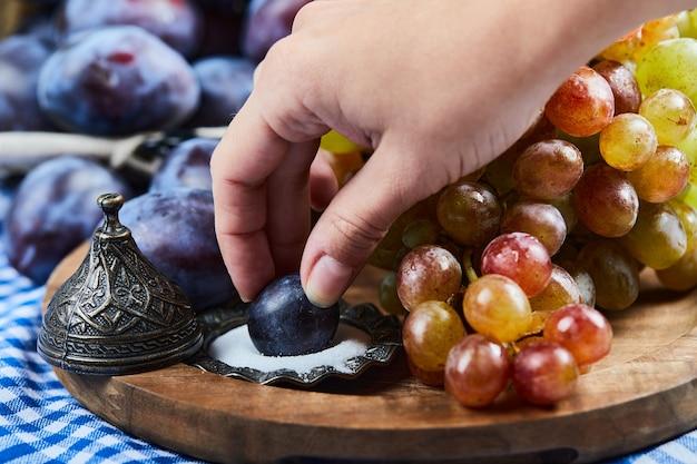 Ameixas frescas, um cacho de uvas e sal em uma placa de madeira.
