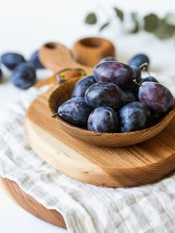 Ameixas maduras azuis tigela de madeira cheia na placa de madeira