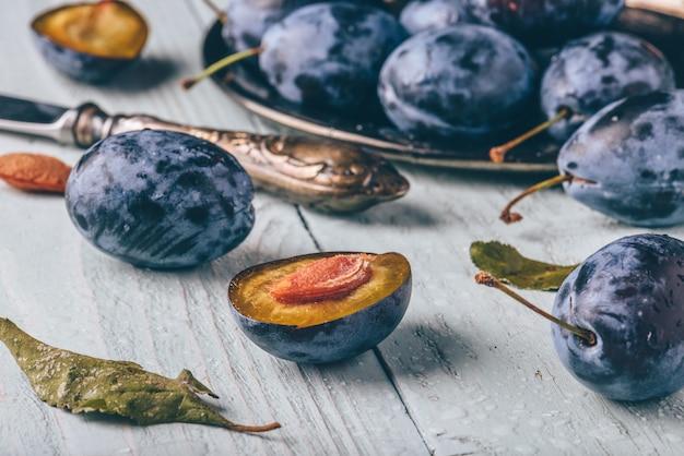 Ameixas maduras com frutas fatiadas, folhas e faca vintage sobre superfície de madeira clara