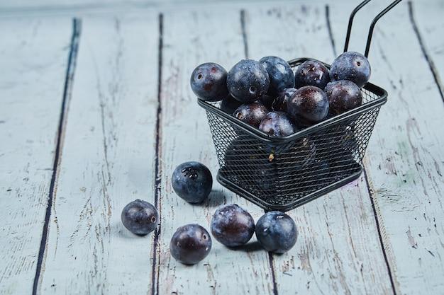 Ameixas maduras de jardim em uma mesa azul