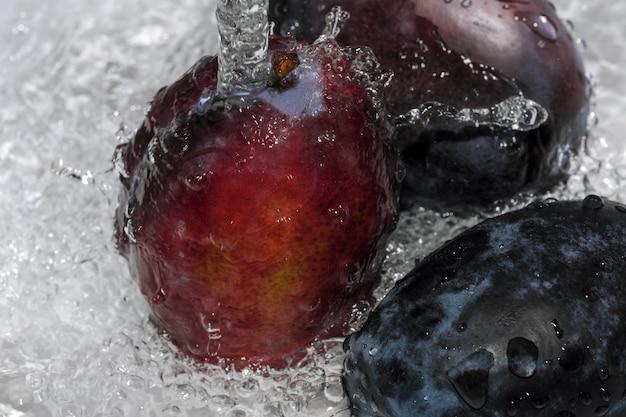 Ameixas maduras e doces são lavadas em um jato de água limpa, close-up macro fotografia