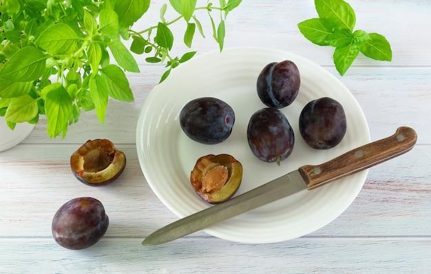 Ameixas maduras e faca em um prato branco e ervas de cozinha em uma superfície de madeira pintada de azul.