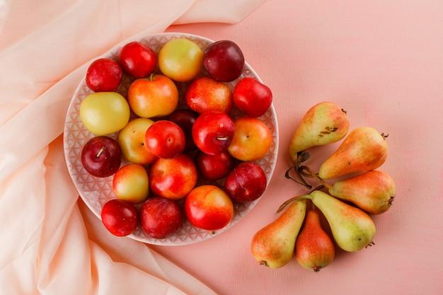 Ameixas maduras em um prato com peras