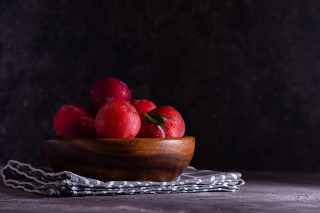 Ameixas maduras em uma placa de madeira com orvalho com um guardanapo de tecido sobre um fundo cinza em tom discreto