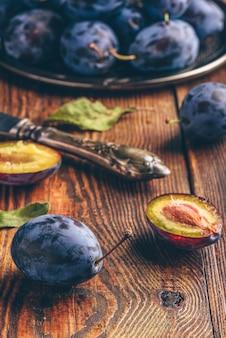 Ameixas maduras na bandeja de metal e superfície de madeira escura com folhas e faca vintage