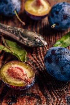 Ameixas maduras na mesa de madeira com folhas, gotas de água e uma faca vintage